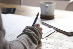אישה כותבת במחברת, קפה על השולחן