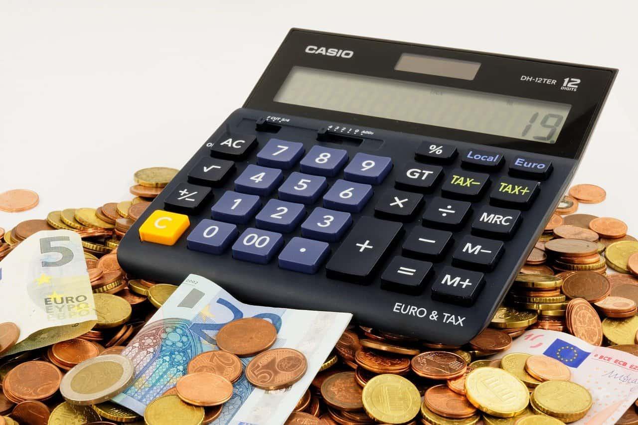 מחשבון ומטבעות כסף על רקע לבן